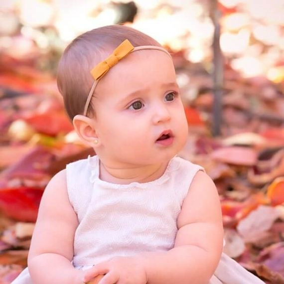 Baby bow on a baby girl sitting in leaves