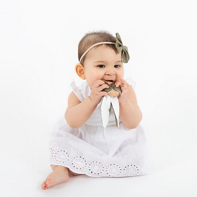 baby with wooden bunny teething ring